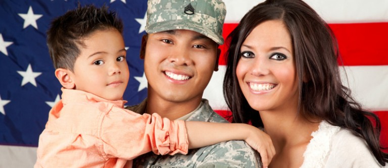 A close-up photo of a happy family of three people. In the middle is the father and he is a veteran. They are in front of a large American flag.