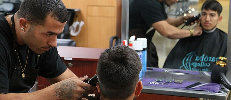 Student learning Barbering at Paroba by working on a client.