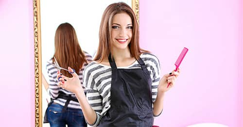 A cosmo student holding scissors and a comb