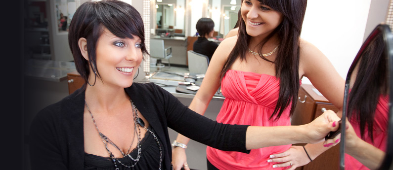 A 30-something woman with a great smile and attractive eyes admires her new hair style while her stylist proudly looks on